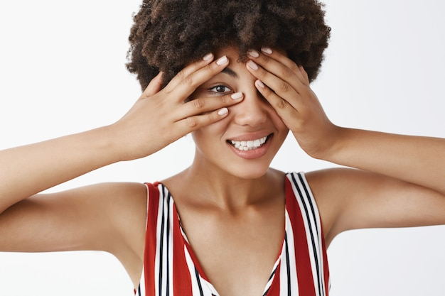Портрет симпатичной темнокожей девушки с вьющейся стрижкой, прикрывающей глаза ладонями и выглядывающей сквозь пальцы, стиснув зубы, чувствуя себя напряженно
