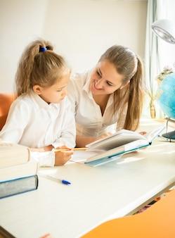 母と宿題をしているかわいい娘の肖像画