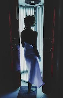 モダンなサンルームで日焼けを楽しんでいるかわいいエレガントな若い女性の肖像画。垂直ソラリウムの健康な若い女性は、喜びを得て楽しんでいます。健康的なライフスタイルと美しく手入れの行き届いた肌のコンセプト