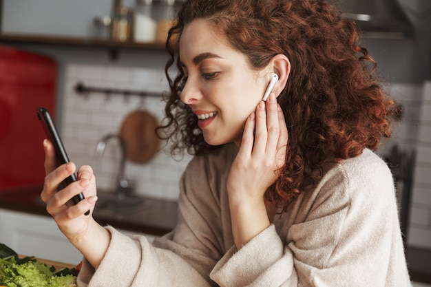 Портрет милой европейской женщины с наушниками, слушающей музыку на мобильном телефоне во время приготовления пищи в интерьере кухни дома