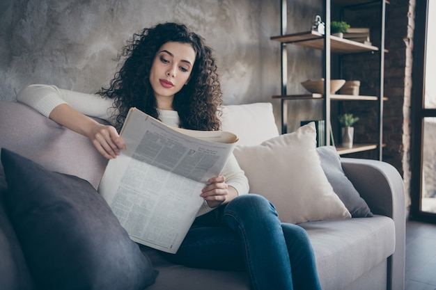 Портрет милой сосредоточенной мирной девушки, сидящей на диване и читающей дайджест новостей в современном индустриальном стиле лофта в помещении