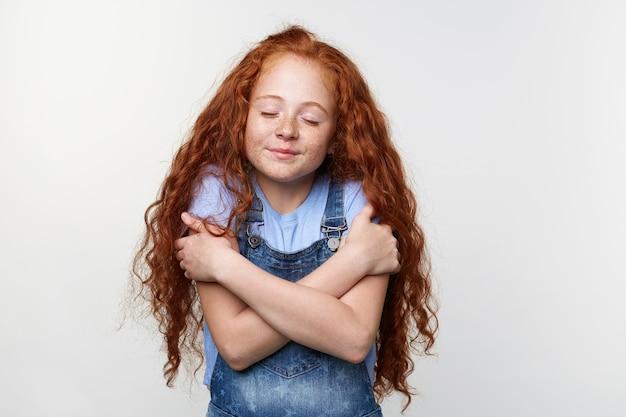Портрет милой веснушчатой маленькой девочки с рыжими волосами, обнимает себя и мечтает о щенке с закрытыми глазами, стоит на белом фоне и мечтательно улыбается.