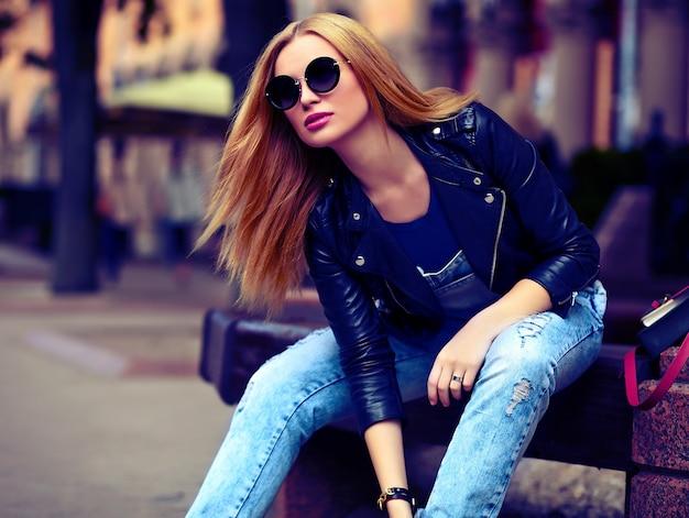 Портрет милые смешные современные сексуальные городские молодые стильные улыбающиеся женщина девушка модель в яркой современной ткани на открытом воздухе, сидя в парке в джинсах на скамейке в очках