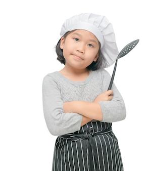 かわいい女の子シェフの肖像画は、料理の帽子とエプロンスタンドと笑顔で隔離された食器を保持