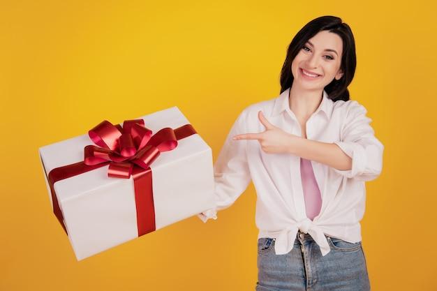かわいい女の子の直接指の肖像画は、黄色の背景にプレゼントボックスを示しています