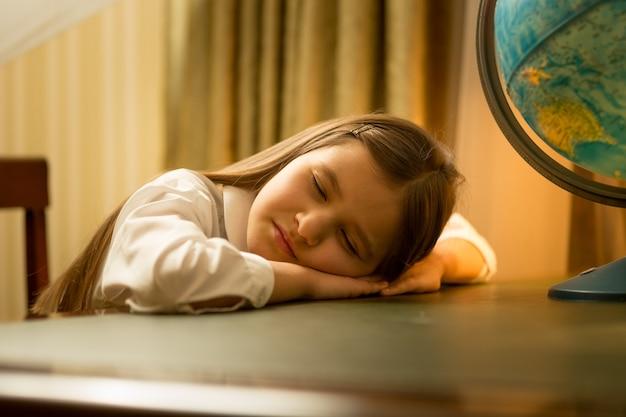 かわいい女の子の肖像画は宿題をしながら眠りに落ちました