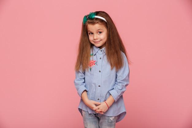 친절한 미소로 찾고 긴 적갈색 머리를 가진 귀여운 소녀의 초상