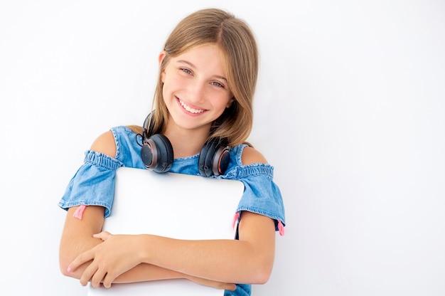 閉じたラップトップを保持しているかわいい女の子の肖像画