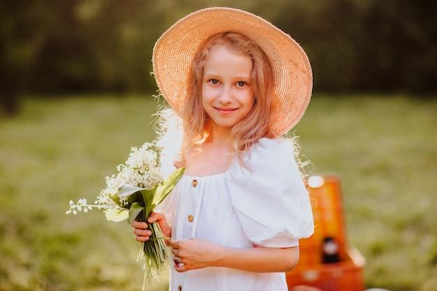 公園で花の花束を保持している夏の帽子のかわいい女の子の肖像画。コピースペース。