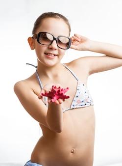 Портрет милой девушки в солнцезащитных очках, показывающей красные морские звезды под рукой