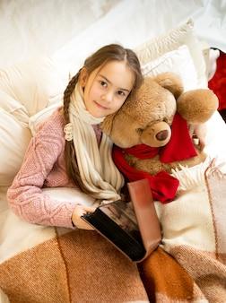 ベッドでテディベアに本を読んでいるかわいい女の子の肖像画