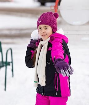 Портрет милой девушки, бросающей снежок