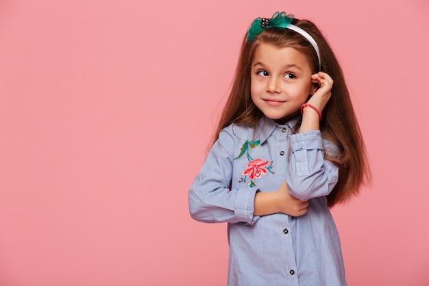 친절한 사랑스러운 미소로 그녀의 긴 적갈색 머리를 만지고 귀여운 소녀의 초상