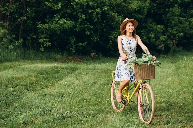 自転車を運転して帽子で金髪の巻き毛を持つかわいい女の子の肖像画。アクティブな人々。屋外。田舎の香りの花、夏のライフスタイルで自転車の美しい少女。クローズアップ
