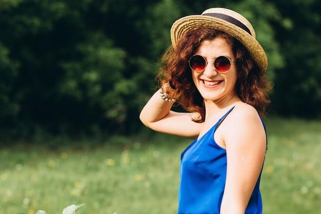 自転車を運転する帽子の巻き毛を持つかわいい女の子の肖像画。アクティブな人々。屋外。田舎の香りの花、夏のライフスタイルで自転車の美しい少女。クローズアップ
