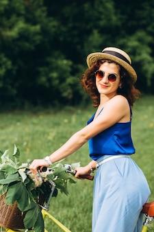 自転車を運転する帽子の巻き毛を持つかわいい女の子の肖像画。アクティブな人々。屋外。