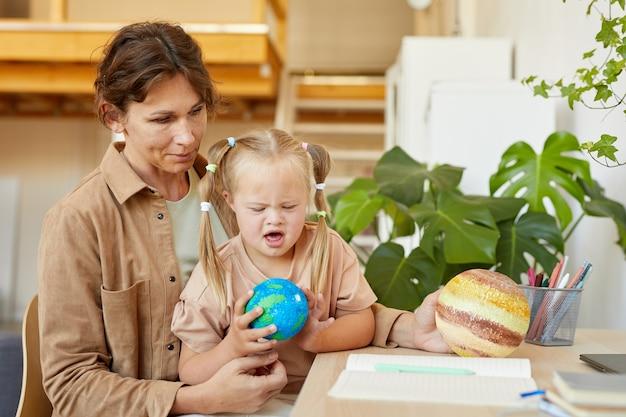 Портрет милой девушки с синдромом дауна, держащей модель планеты во время учебы дома с матерью, копией пространства