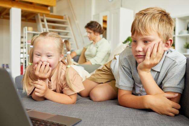 노트북 화면을보고 집에서 형제와 함께 소파에 누워있는 동안 행복하게 웃는 다운 증후군을 가진 귀여운 소녀의 초상화