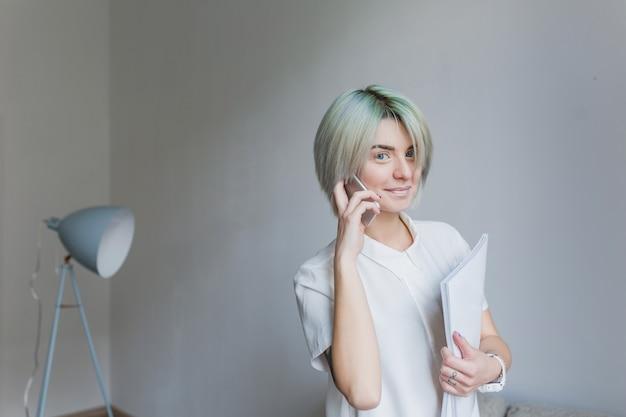 灰色のスタジオで書類を歩いて灰色の短い髪型でかわいい女の子の肖像画。彼女は白いドレスと軽い化粧を着ています。彼女は電話で話し、カメラに微笑んでいます。