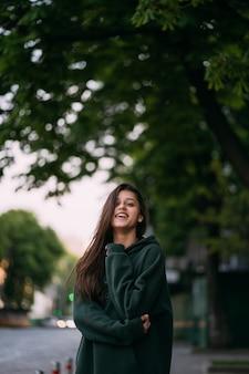 長い髪のかわいい女の子の肖像画は通りの都市でカメラを見てください。