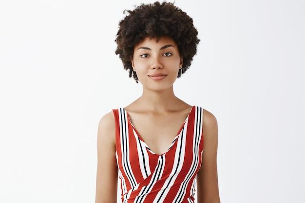 Портрет симпатичной красивой молодой афроамериканки в полосатом наряде, улыбающейся с небрежным беззаботным и расслабленным выражением лица над серой стеной