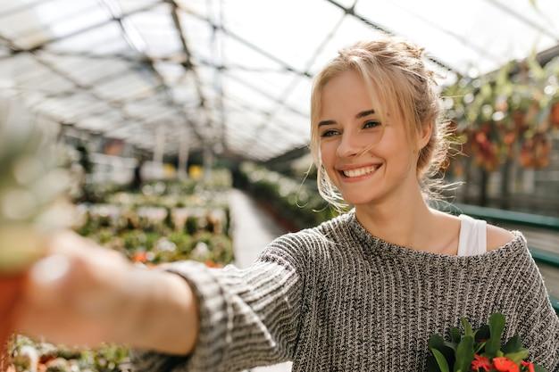 笑顔でかわいい緑色の目の女性の肖像画は温室でポーズをとって植物を保持します。