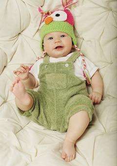 Портрет милого счастливого 5-месячного ребёнка с забавной шляпой. фотография смешной малышки.