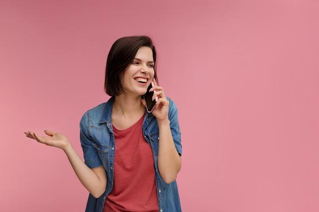 Портрет милой счастливой брюнетки в футболке и джинсовой рубашке