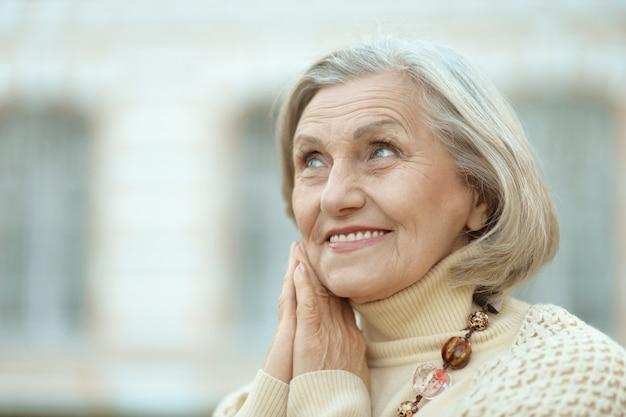 かわいい幸せな年配の女性の屋外の肖像画