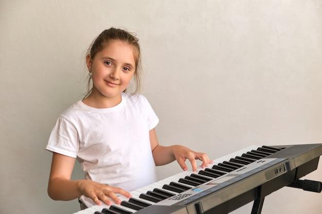 エレクトリックピアノを弾くかわいい幸せな笑顔の女の子の肖像画
