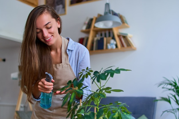 Портрет милой счастливой молодой привлекательной женщины в фартуке, поливающей комнатные растения из пульверизатора
