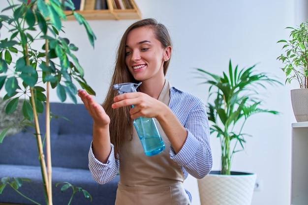 スプレーボトルを使用して観葉植物に水をまくエプロンでかわいい幸せな若い笑顔の魅力的な女性庭師の肖像画