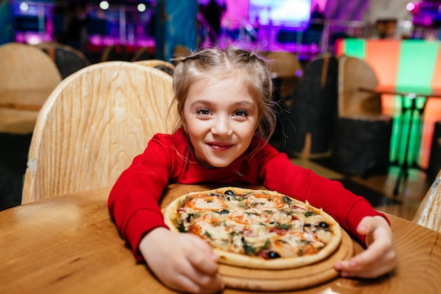 Портрет милой голодной счастливой улыбающейся маленькой девочки, ребенок ест вкусную пиццу в ресторане