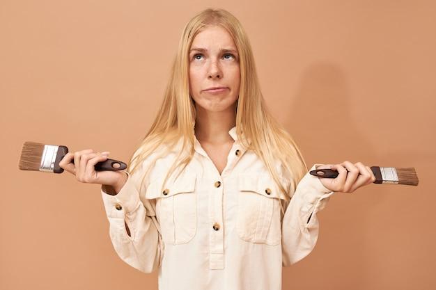 Портрет симпатичной нерешительной молодой женщины с прямыми светлыми волосами, позирующей изолированно с кистями, смотрящей вверх с задумчивым выражением лица, сомневающейся