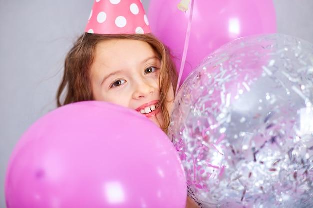 Портрет милой, радостной маленькой девочки в розовом платье и шляпе играет с воздушными шарами дома