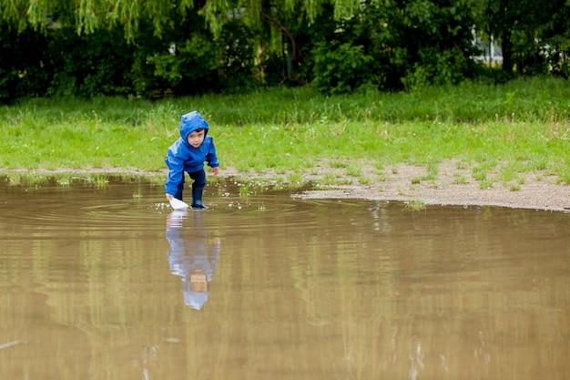 Портрет милого мальчика малыша играя с кораблем ручной работы. мальчик из детского сада плывет на игрушечной лодке у кромки воды в парке.