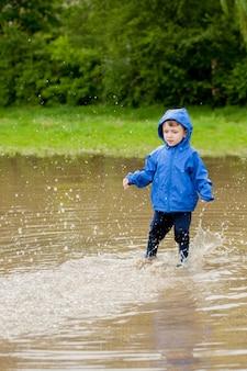 手作りの船で遊ぶかわいい男の子の肖像画。公園の水際でおもちゃのボートを航行する幼稚園の少年。