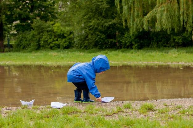 Портрет милого мальчика малыша играя с кораблем ручной работы. детский сад мальчик плывет на игрушечной лодке у кромки воды в парке.