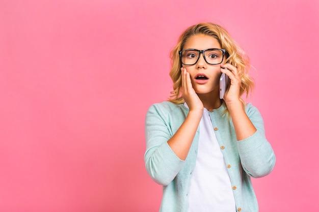携帯電話を使用してピンクの背景の上に孤立して立っているかわいい子供の十代の少女の肖像画。