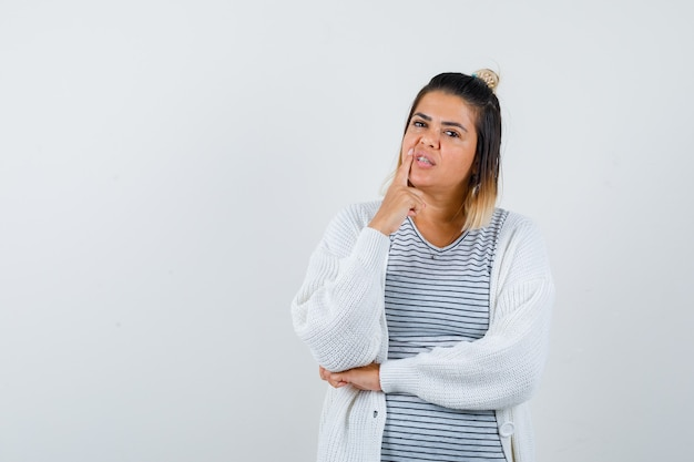 Tシャツ、カーディガン、思いやりのある正面図で指を口の近くに保つかわいい女性の肖像画