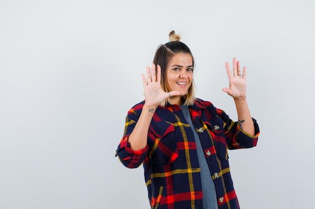 チェックシャツで降伏ジェスチャーを示して幸せそうに見えるかわいい女性の肖像画