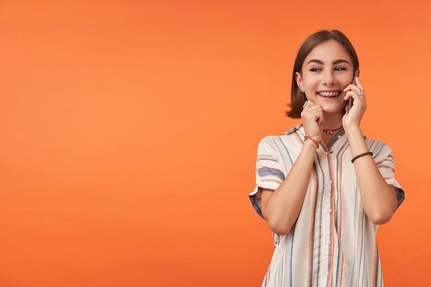 줄무늬 셔츠, 치아 교정기 및 팔찌를 착용하고 전화에 귀여운 아가씨 이야기의 초상화. 웃고 턱을 만지고. 복사 공간에서 왼쪽을보고 주황색 벽 위에 서서