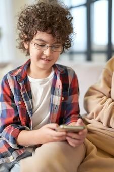 Портрет милого латинского мальчика в очках, улыбаясь при использовании смартфона, сидя дома. технологии, детство, концепция домашнего обучения