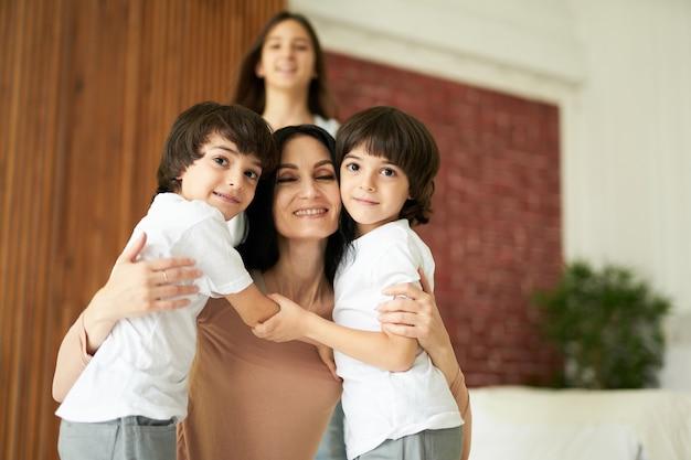 Портрет милых латинских детей, маленьких мальчиков-близнецов, смотрящих в камеру и обнимающих свою маму, проводящих время вместе дома. семья, концепция детства