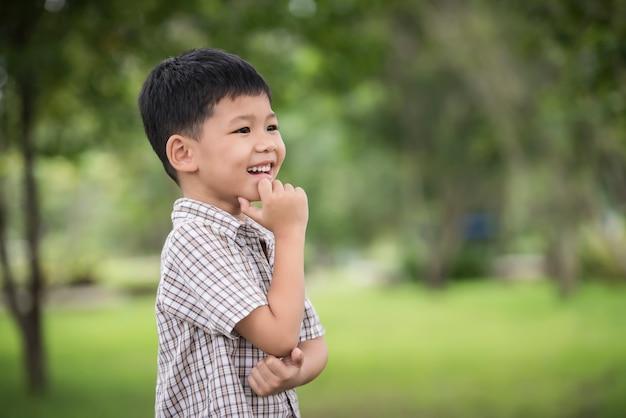 かわいいアジア人少年の手の顎の下での肖像画と思って立っている間
