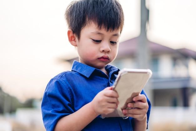 Портрет милого маленького азиатского мальчика, расслабляющегося с помощью цифрового смартфона.