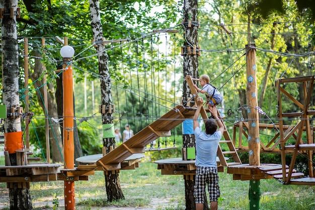 Портрет милый маленький мальчик и девочка ходить на веревочный мост в парке приключений канат.
