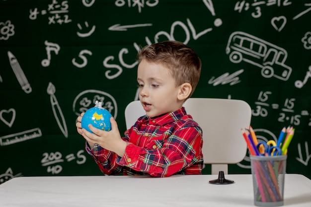 黒板の背景に小さな地球を手で保持しているかわいい男の子の肖像画。学校の準備ができています。学校に戻る。