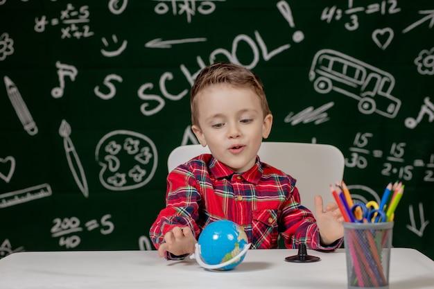 黒板背景に小さな地球を手で保持しているかわいい男の子の肖像画。学校の準備ができています。学校に戻る。