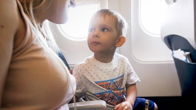 飛行機に座っている彼の母親を見ているかわいい男の子の肖像画。